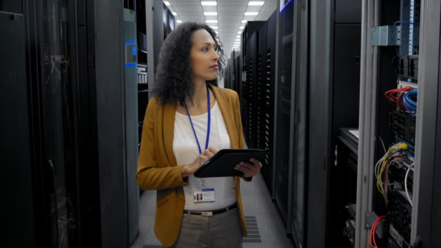 Female IT engineer checking the servers in the server room