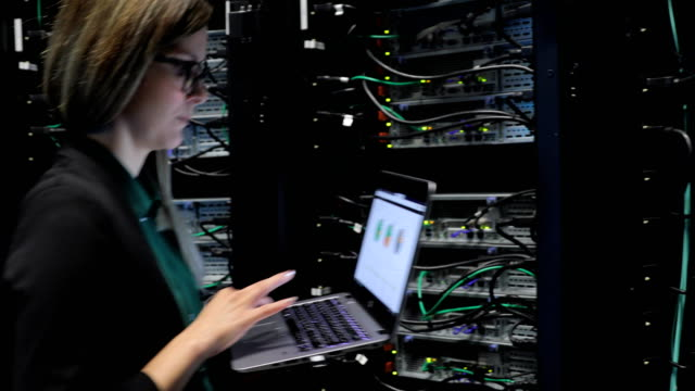 Female IT Engineer Coming into Server Room with her Laptop
