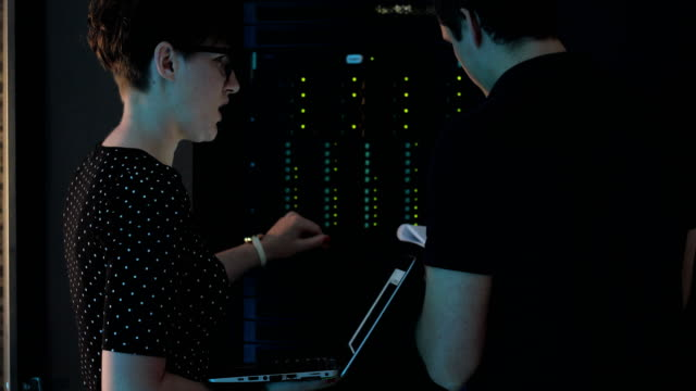 Female IT Engineer Explaining and Teaching a Young Man How to Work with Super Computer