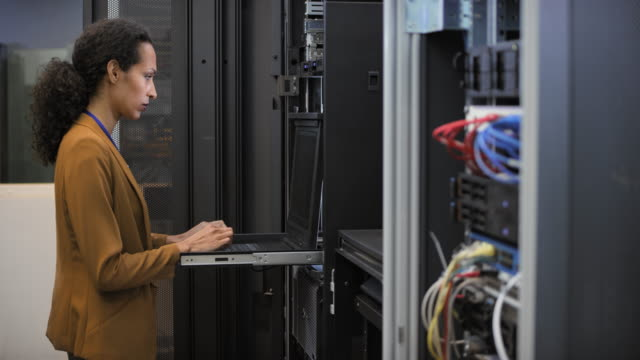 ds female it engineer working on a laptop in the server room - tecnico video stock e b–roll