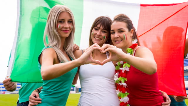 CU female italian sport fans at soccer stadium making heart shape