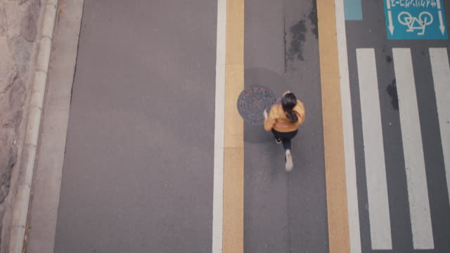 female japanese runner sprinting on sidewalk in tokyo, japan. - high angle view stock-videos und b-roll-filmmaterial