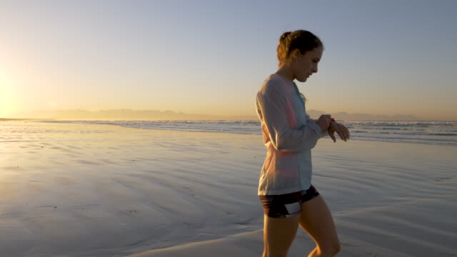 female jogger checking time on her watch - wearable computer stock videos & royalty-free footage