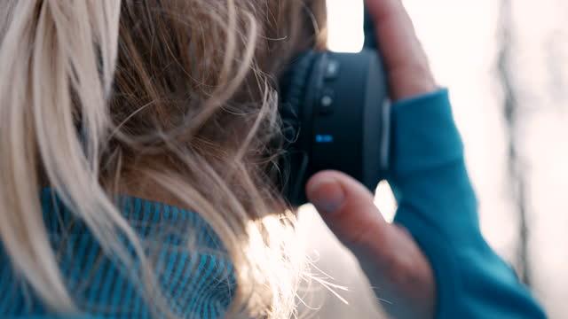 vídeos y material grabado en eventos de stock de slo mo jogger hembra ponerse auriculares antes de empezar a correr en el bosque - auriculares una persona escapismo vista posterior cabeza y hombros