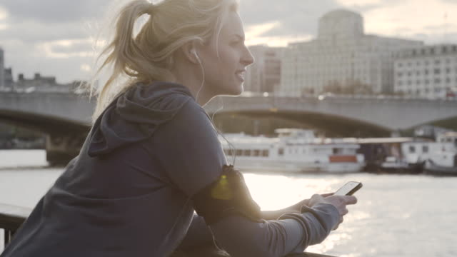 Female jogger stops running to take photos on mobile phone at embankment.