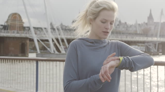 Female jogging along embankment, stops to look at fitness watch, then carries on jogging.