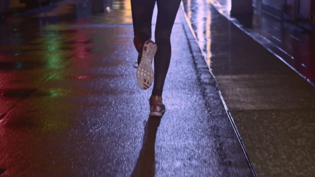 slo mo tu ts female jogging in the city at night - jogging stock videos & royalty-free footage