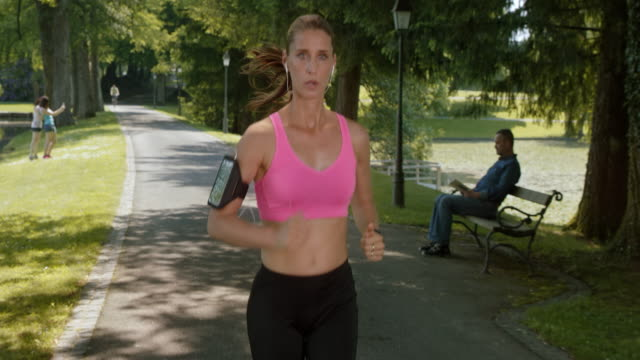 SLO MO TS TU Female jogging in the park along a beautiful lake