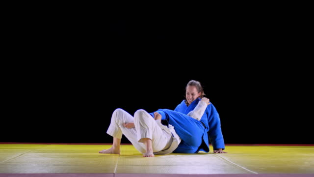 slo mo female judoist in blue outfit holding her opponent on the floor using her legs - females stock videos & royalty-free footage