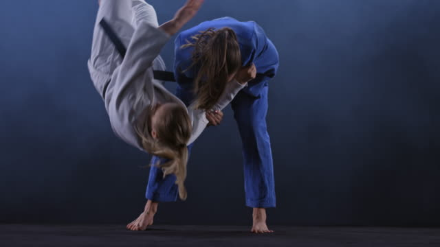 vídeos de stock e filmes b-roll de slo mo ld female judoka in blue outfit throwing her opponent on the floor - contestant