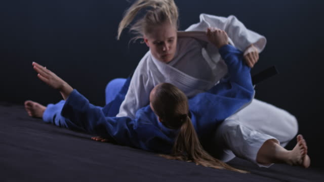 slo mo female judoka in white outfit throwing her opponent in blue on the floor - effort stock videos & royalty-free footage