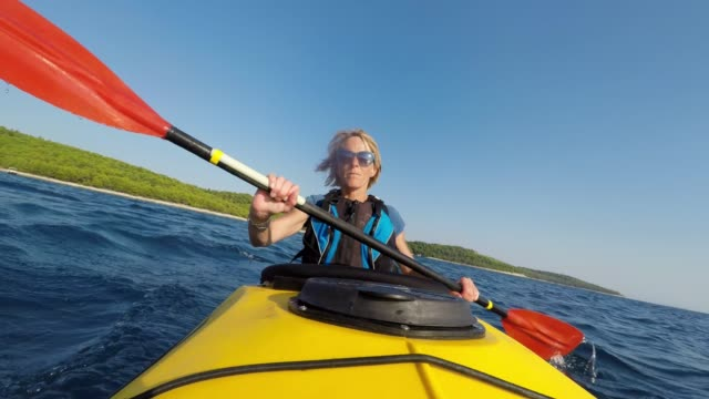 vídeos de stock e filmes b-roll de ld female kayaker paddling a yellow sea kayak in sunshine - kayaking
