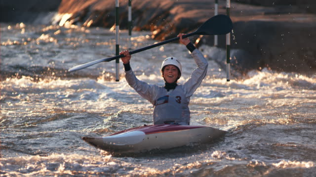 SLO MO Female kayaker paddling into the finish and raising her hands