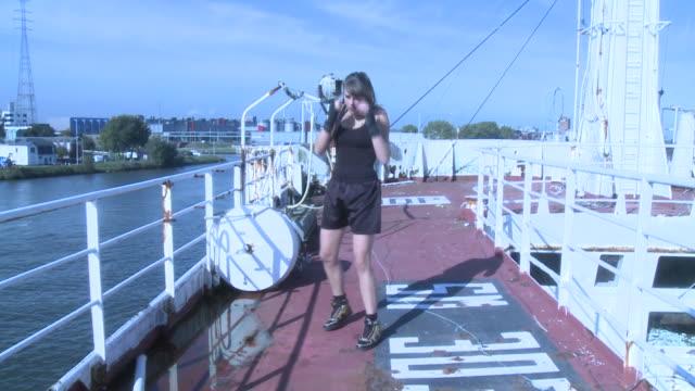 ms female kickboxer practicing kicks and punches on ship's deck, gent, belgium - 女子ボクシング点の映像素材/bロール