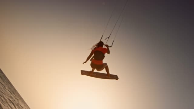slo mo female kiteboarder doing a grab while airborne at sunset - extreme sports stock videos & royalty-free footage