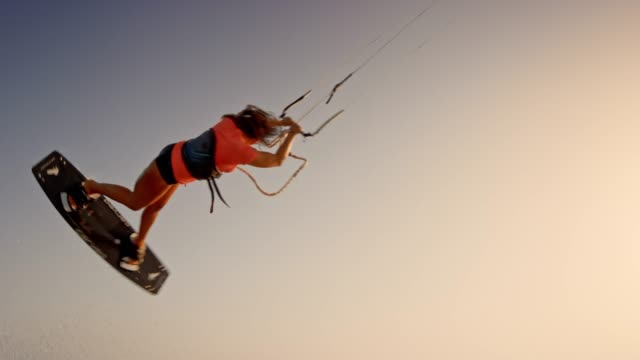 SLO MO Female kiteboarder jumping and turning at sunset