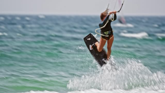 female kiteboarder jumping into the air and doing a turn - kiteboarding stock videos & royalty-free footage