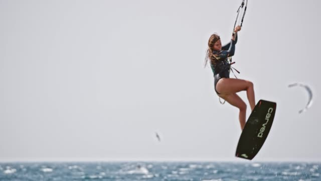 slo mo female kiteboarder jumping into the air and turning - skill stock videos & royalty-free footage