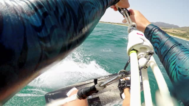 POV Female kiteboarder jumping into the air in sunshine