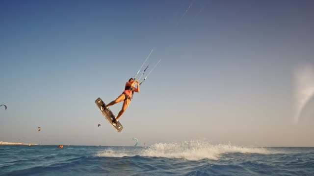 slo mo female kiteboarder popping into the air as the sun is setting - kiteboarding stock videos & royalty-free footage
