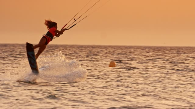SLO MO female kiteboarder popping into the air at sunset