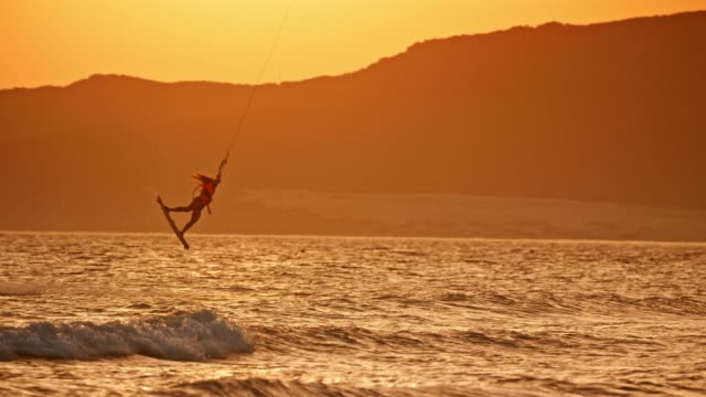 slo mo female kiteboarder riding at sunset jumping into the air and turning - kiteboarding stock videos & royalty-free footage