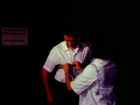 female lab assistant strapping sensors to ankles of man / woman fastening strap to chest of man, leading him into adjacent room and into car parked... - hinweisschild stock-videos und b-roll-filmmaterial