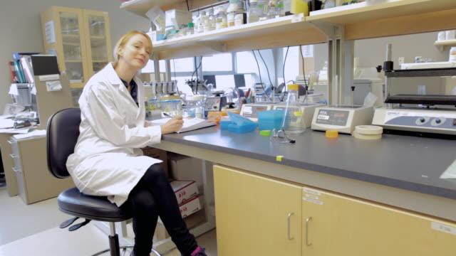 ms pov female lab technician sitting at cancer research healthcare medicine industry dna sequencing laboratory / vancouver, bc, canada    - laborkittel stock-videos und b-roll-filmmaterial