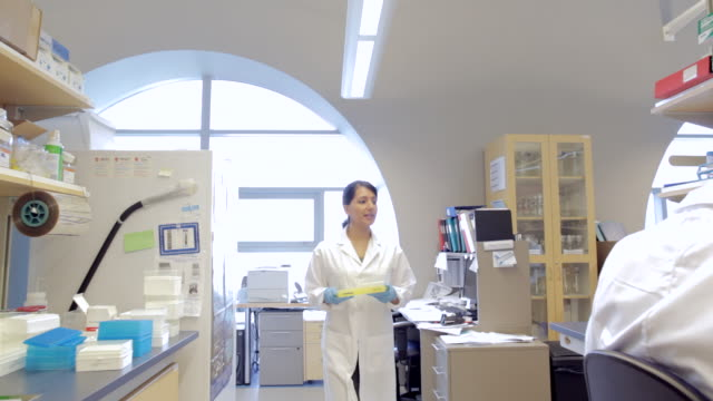 MS POV Female Lab technician walking with samples at Cancer research Healthcare medicine Industry DNA sequencing Laboratory / Vancouver, BC, Canada