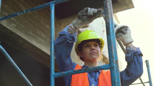 weibliche arbeit befestigung metallgerüst eatorieren vor ort - baugerüst stock-videos und b-roll-filmmaterial