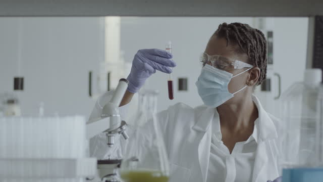female laboratory scientist conducts experiment in science lab looking at blood sample with coronavirus - microbiology stock videos & royalty-free footage