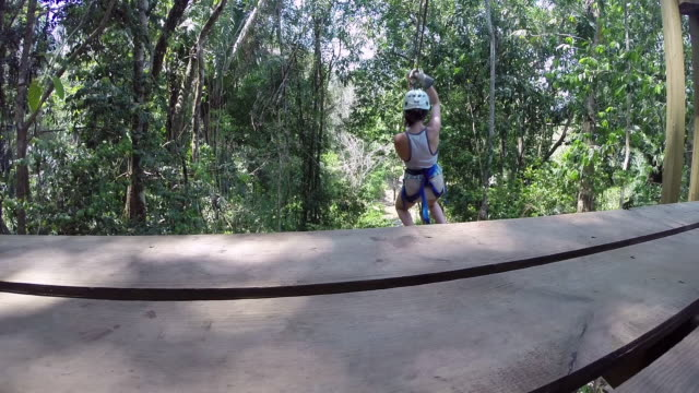 Female launches down a zip-line in jungle