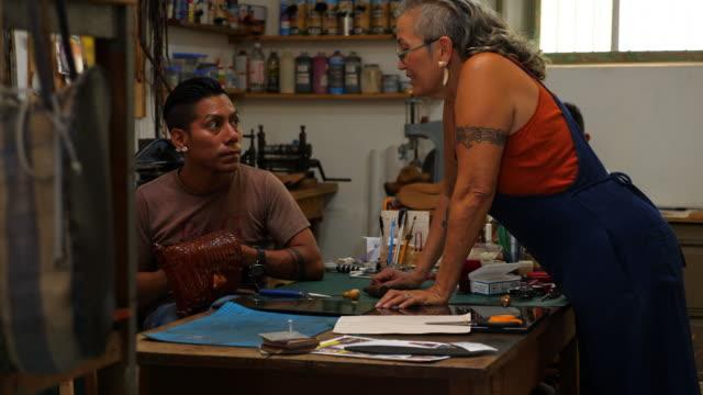 vídeos y material grabado en eventos de stock de ms female leather shop owner assisting employee with design of purse in workshop - mérida méxico