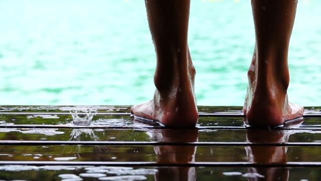 vídeos de stock, filmes e b-roll de pernas femininas em câmera lenta, a água da piscina - pátio