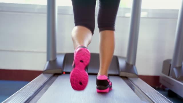 vidéos et rushes de les jambes femelles gros plans en cours d'exécution sur un tapis roulantles femmes jogging dans la salle de gym pour perdre du poids - joggeuse