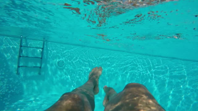 Female legs enjoying in the pool