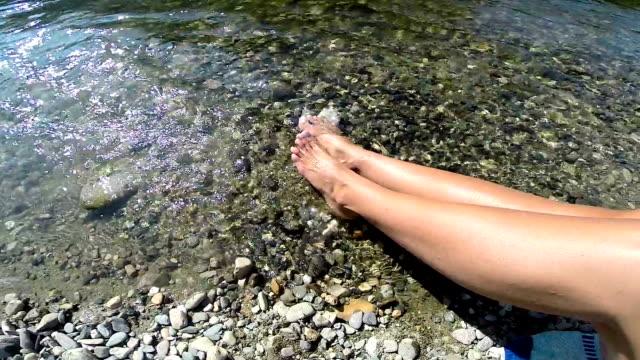 Vrouwelijke benen genieten van het kristalheldere water
