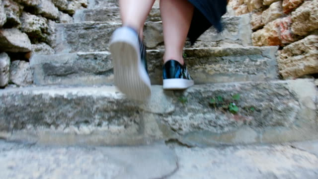 female legs feet walking up stone steps staircase - stone material stock videos & royalty-free footage