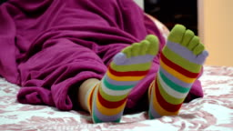 Female legs in socks with toes relaxing in bed