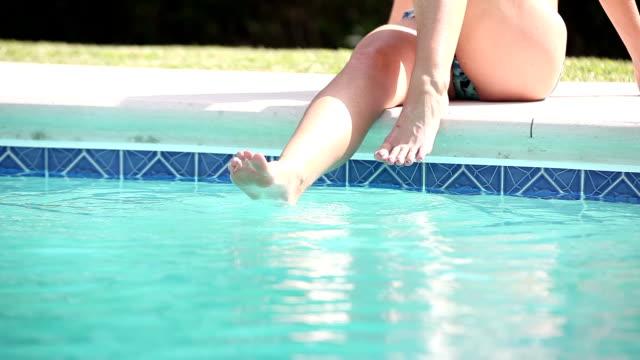 vídeos y material grabado en eventos de stock de mujeres piernas en la piscina. cauasian mujer - mojar