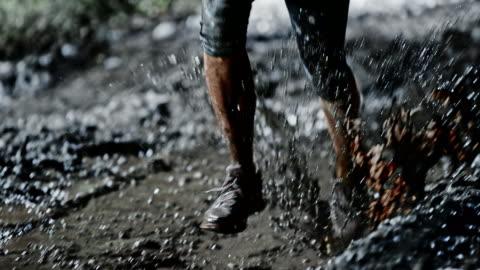 stockvideo's en b-roll-footage met slo mo ds vrouwelijke benen die dwars over een modderig plas bij nacht - tegenspoed