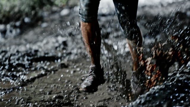 slo mo ds female legs running across a muddy puddle at night - mud stock videos & royalty-free footage