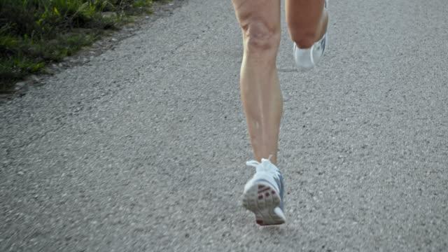 slo mo ts female legs running on asphalt - muscular build stock videos & royalty-free footage