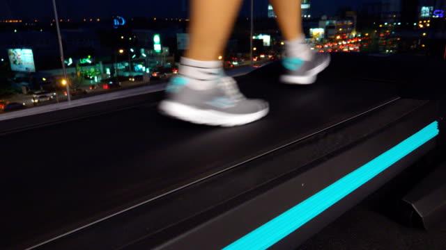 vidéos et rushes de 4k: female legs en cours d'exécution sur la machine de tapis roulant dans une salle de sport à la ville de nuit - amélioration
