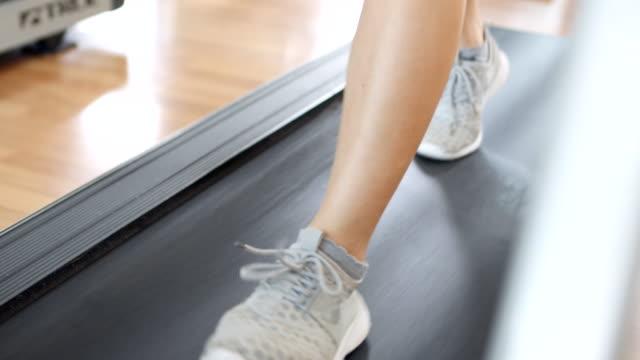 weibliche beine gehen und laufen auf dem laufband - trainingsraum freizeiteinrichtung stock-videos und b-roll-filmmaterial