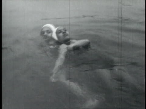 1950 montage female lifeguards practice pulling victim out of water and giving cpr / united states - bagnino video stock e b–roll