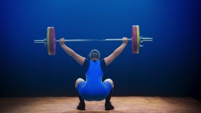 stockvideo's en b-roll-footage met vrouwelijke lifter tillen van de barbell op een wedstrijd - gewicht fysieke beschrijving