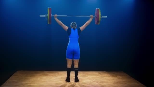 stockvideo's en b-roll-footage met ld vrouwelijke lifter tillen van de barbell op de gewichtheffen concurrentie - gewicht fysieke beschrijving
