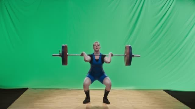 stockvideo's en b-roll-footage met ld vrouwelijke lifter tillen van de barbell het uitvoeren van de schone en ruk lift - gewichten