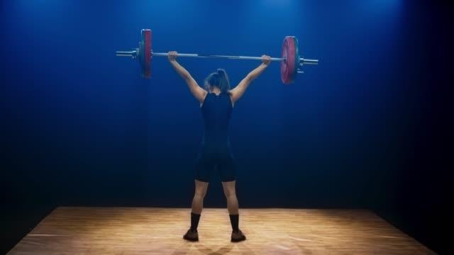 stockvideo's en b-roll-footage met ld vrouwelijke lifter het uitvoeren van de snatch aan de barbell lift op de concurrentie - gewicht fysieke beschrijving